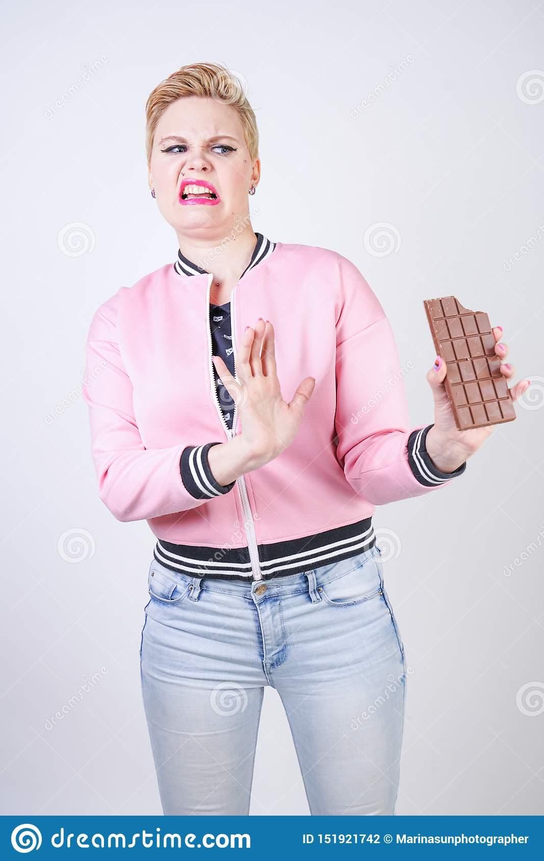 Plus size caucasian girl with short haircut stands in pink sports jacket with chocolate bar in her hands and shows hate emotions f