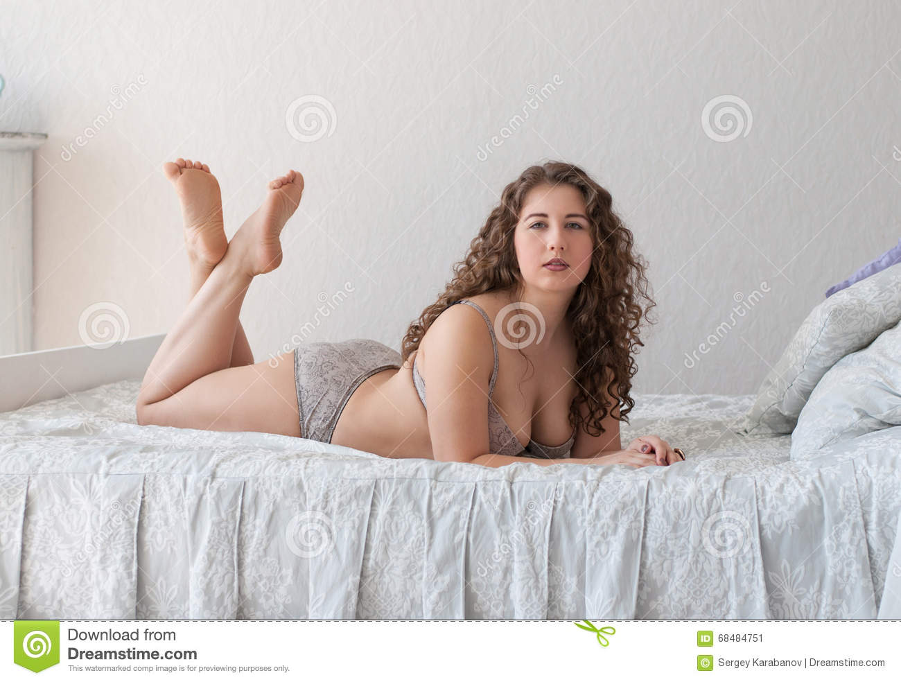 Plus size female in lingerie lying on the bed legs crossed