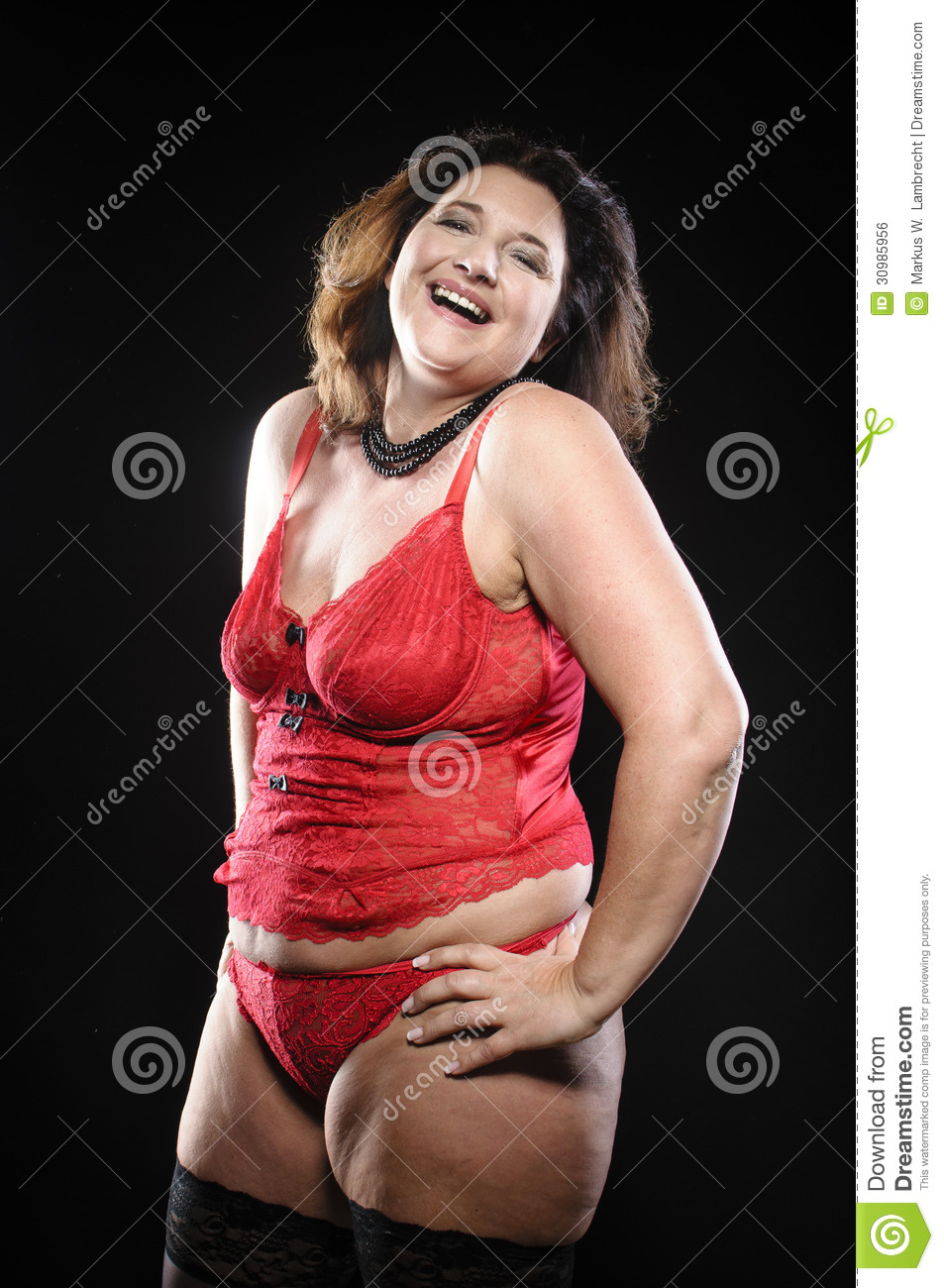 1f2a212b0e8 Attractive adult plus size model wearing red lingerie against black  background and laughs.