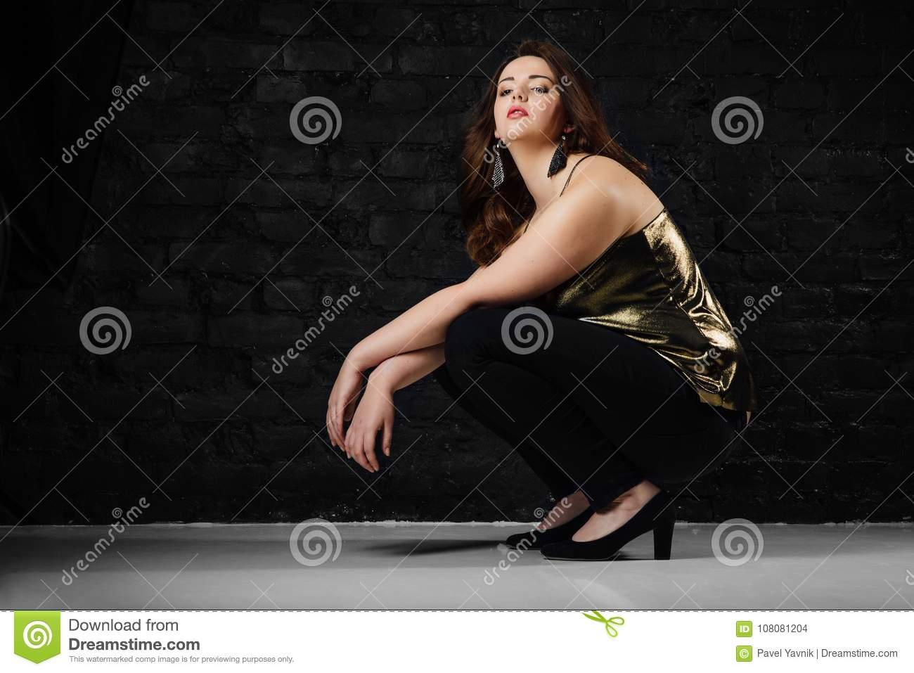 c0272b023d855 Royalty-Free Stock Photo. Plus size model in a gold blouse and black jeans  on a brick loft background.