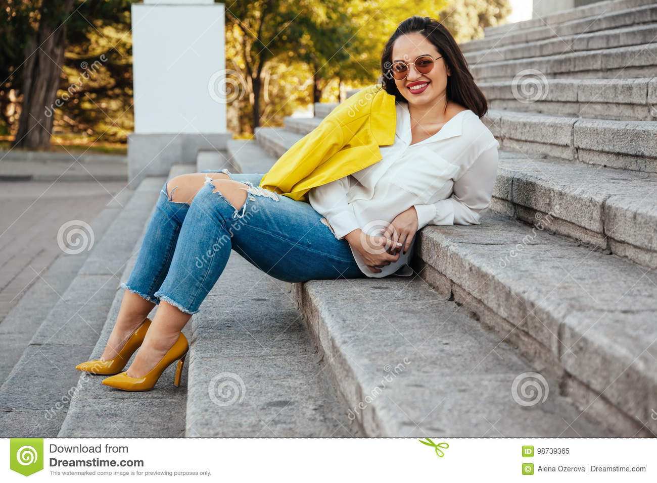123106e060f Prerry young woman wearing bright colorful jacket, ripped jeans and heel  shoes walking on the city street. Casual fashion, plus size model.