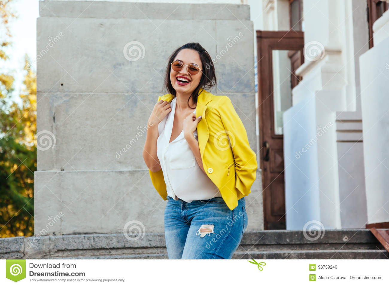 786d79c58e6 Pretty young woman wearing bright colorful jacket walking on the city street.  Casual fashion