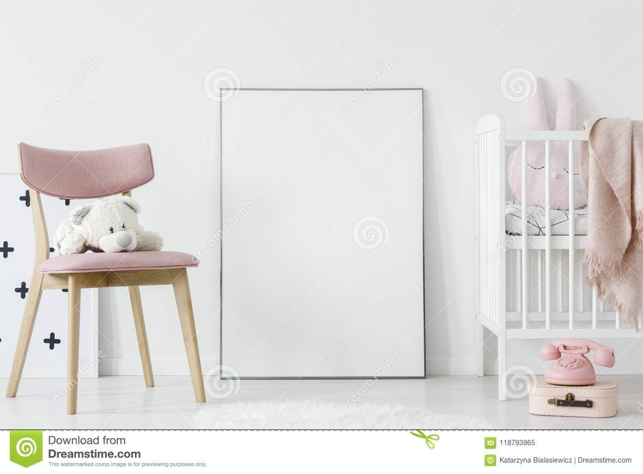 Plush toy on pink chair next to poster with mockup in baby`s roo