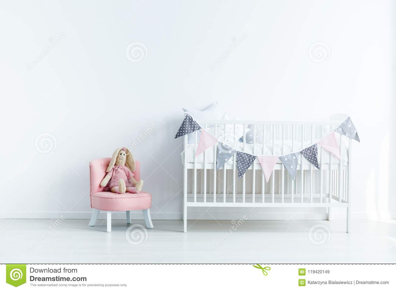 Plush toy on pink chair next to white crib in white baby`s bedro