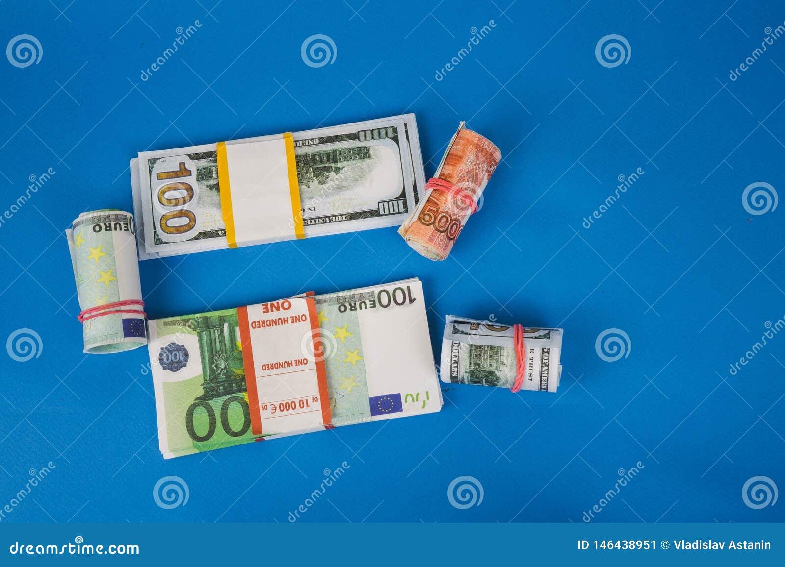 Plusieurs bouchons de l argent de diff?rentes devises sur un fond bleu