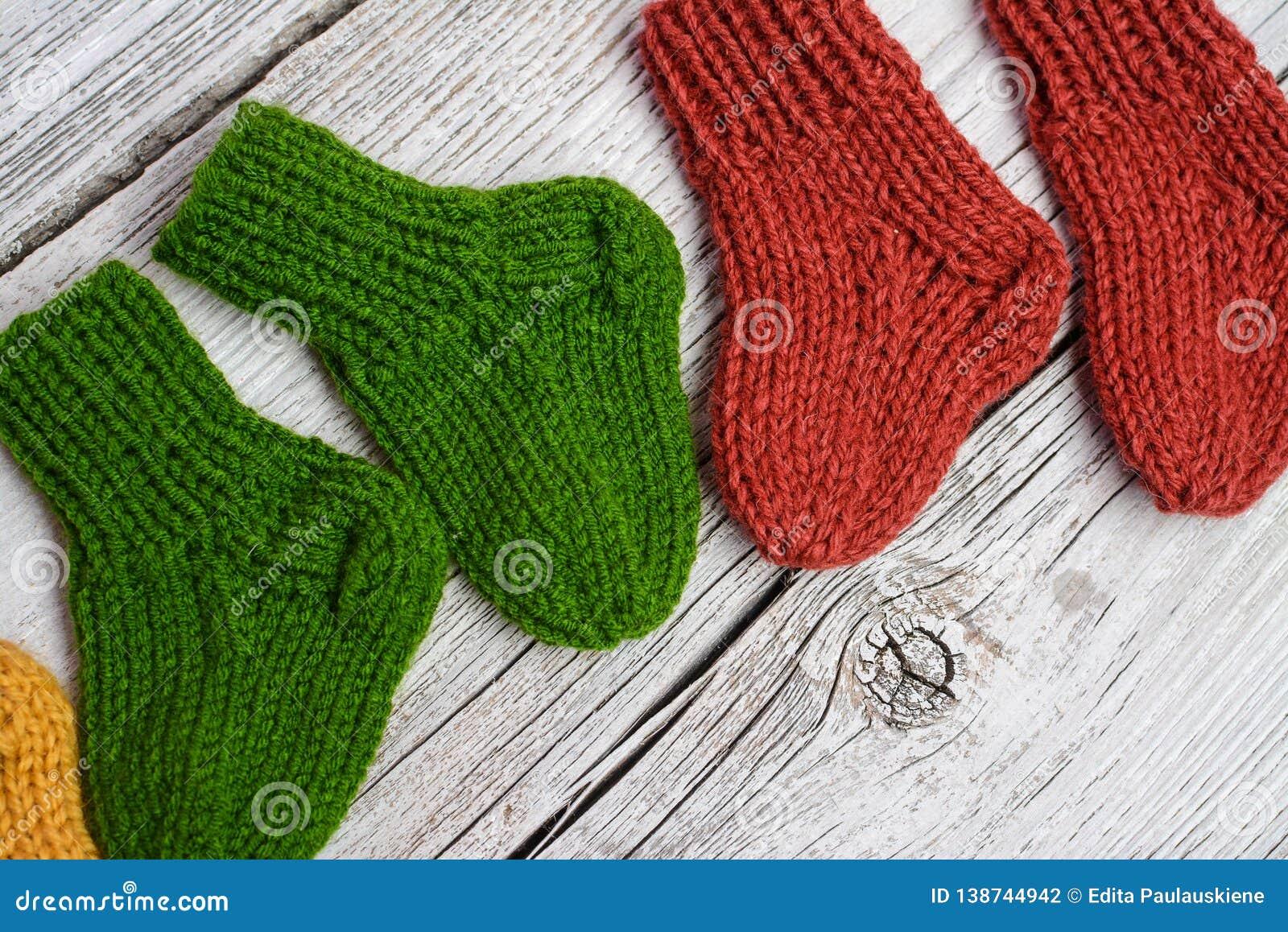 Plusieurs paires de petites chaussettes de laine pour nouveau-né sur la table en bois de cru