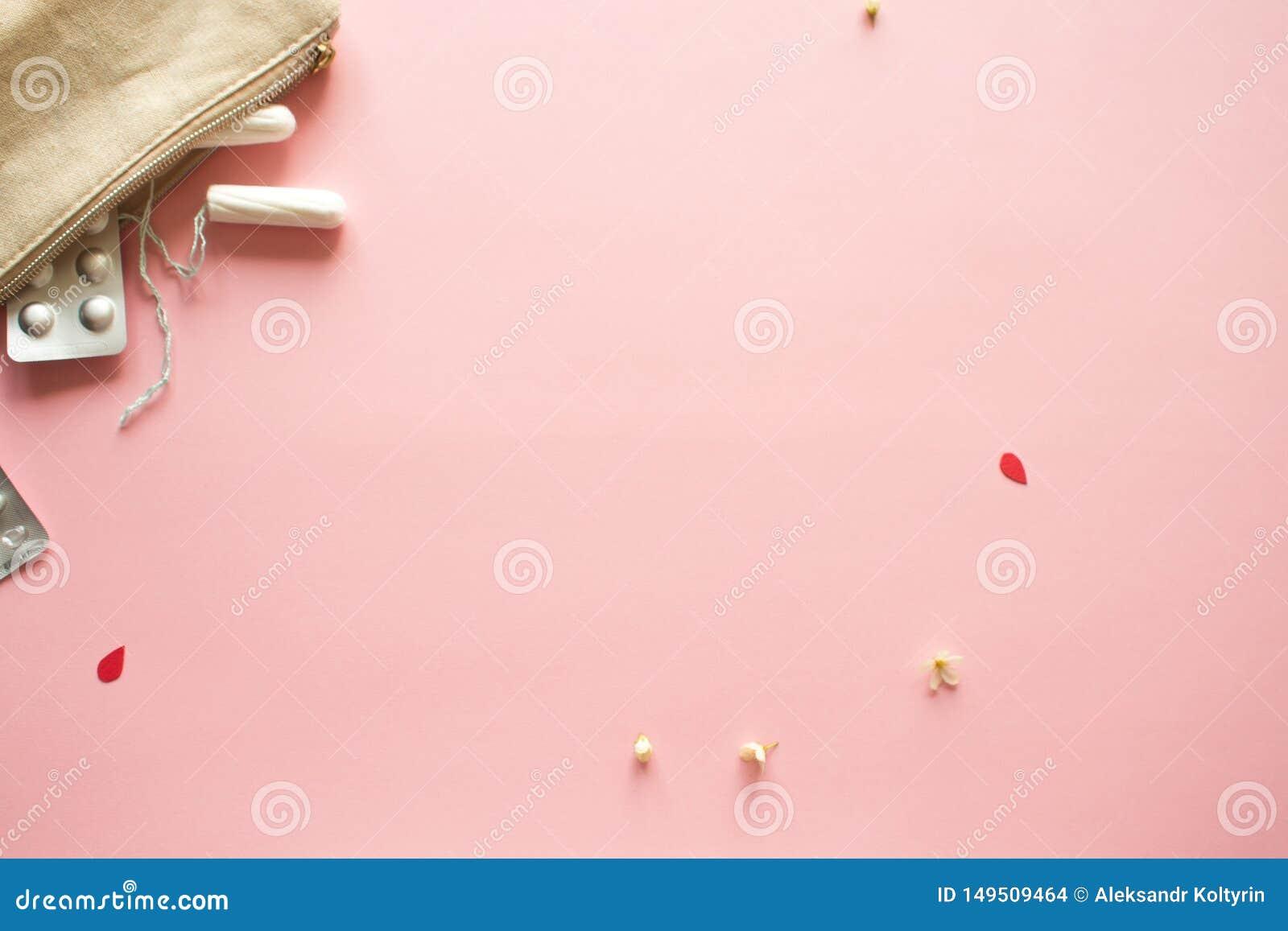 PMS e o conceito cr?tico dos dias Comprimidos de dor e produtos dos cuidados pessoais, fundo cor-de-rosa
