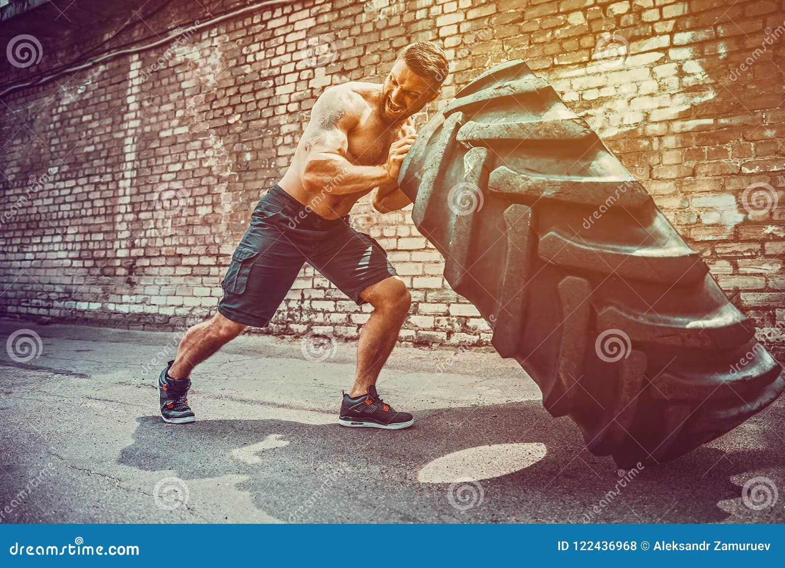 Pneu movente do homem descamisado muscular da aptidão grande no centro do gym, conceito que levanta, treinamento apto da cruz do
