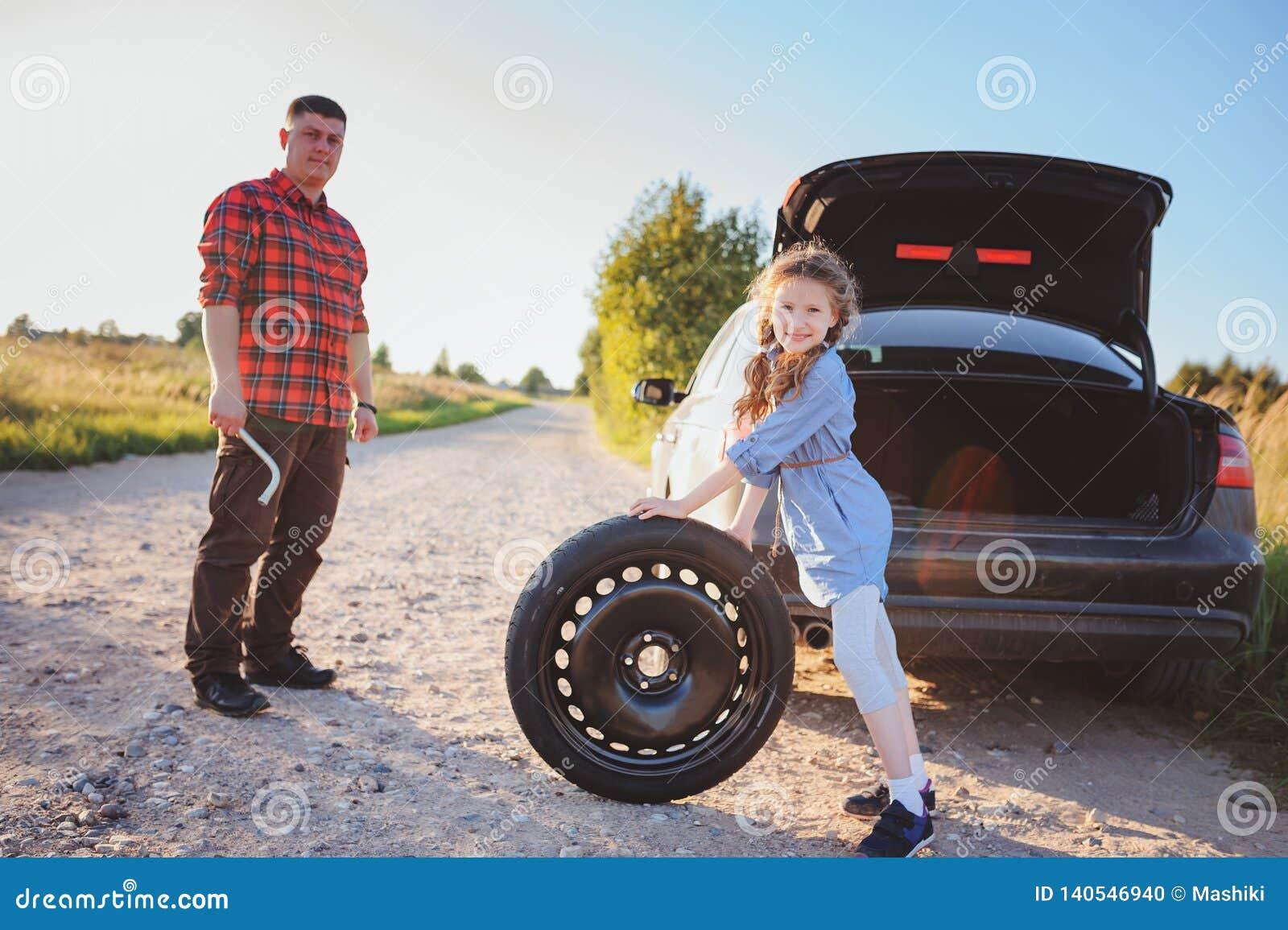 Pneu quebrado em mudança do pai e da filha durante a viagem por estrada rural do verão