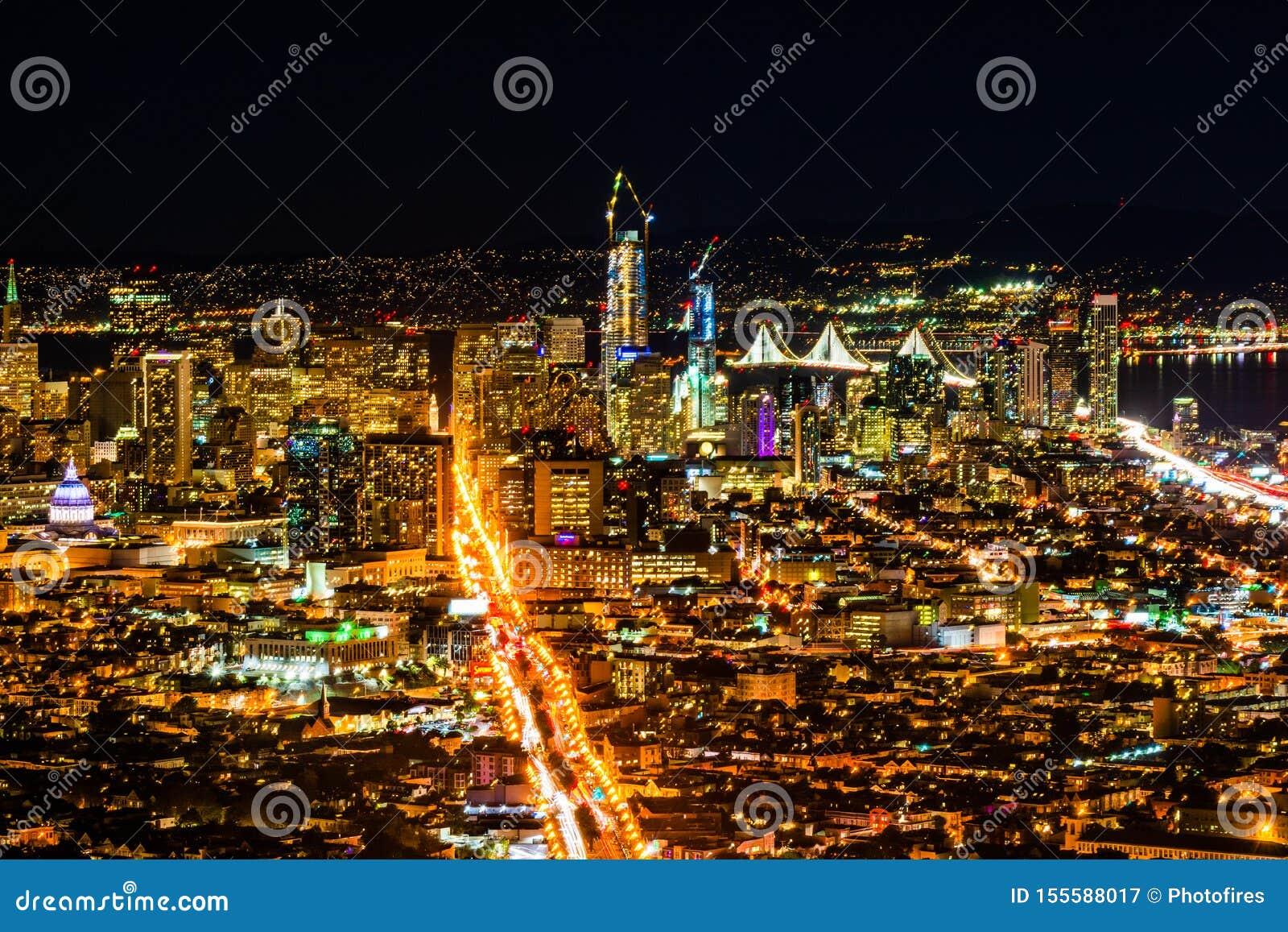 Pnoramic sikt för natt av det San Francisco centret med skyskrapor och den Okeland bron