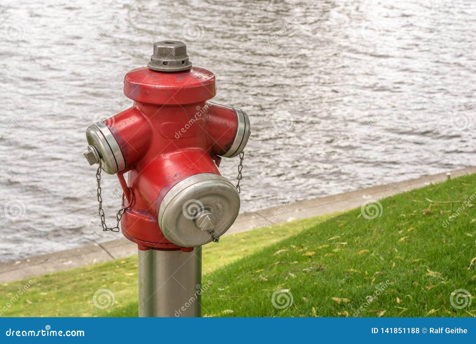 Pożarniczy hydrant z pożarniczym gasidłem w tle