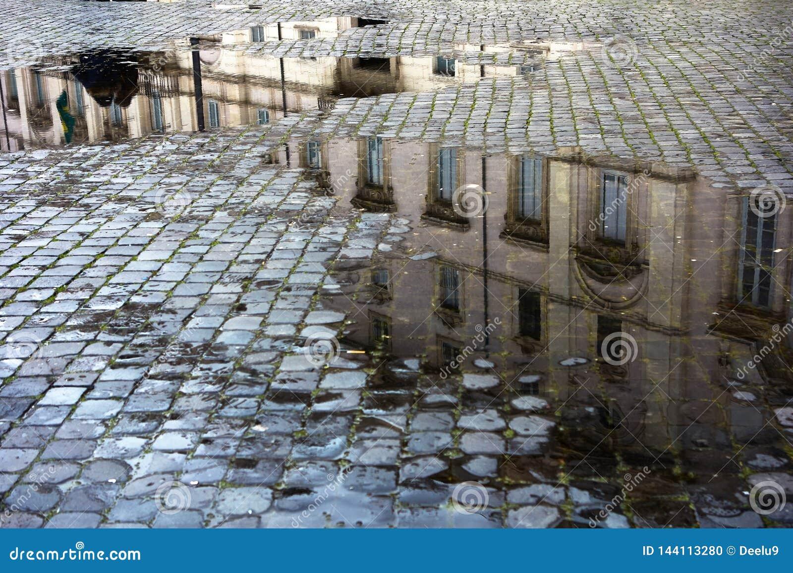 Poças em uma rua cobbled de Roma Itália, próximo
