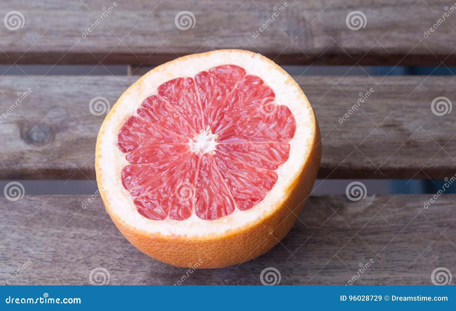 Połówka czerwony grapefruitowy na drewnianym stole