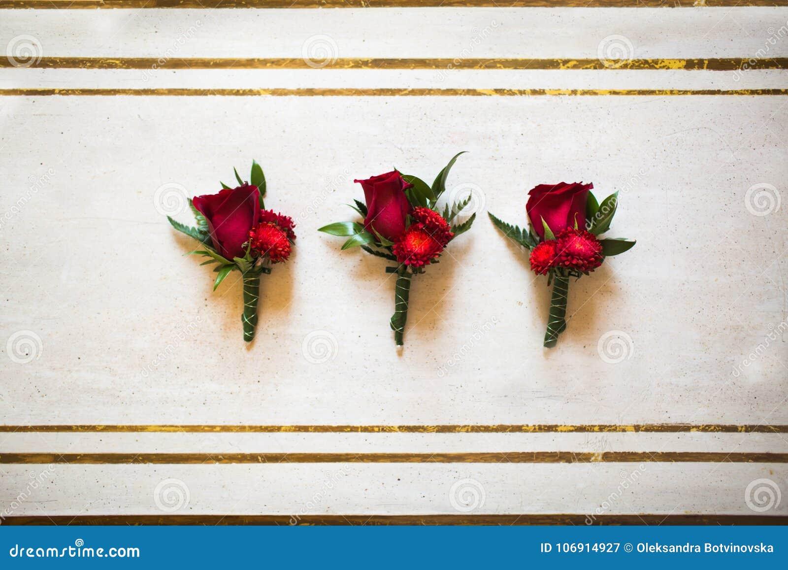 Poślubiać ustawiam trzy boutonnieres czerwone róże na stole