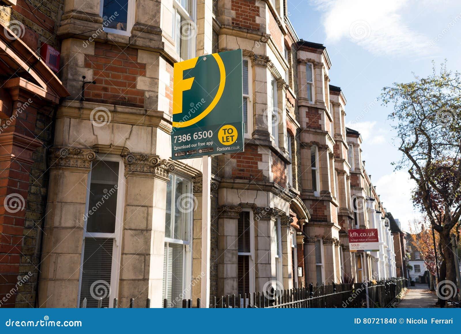 Pośrednik w handlu nieruchomościami podpisuje na zewnątrz rzędu wiktoriański tarasujący domy