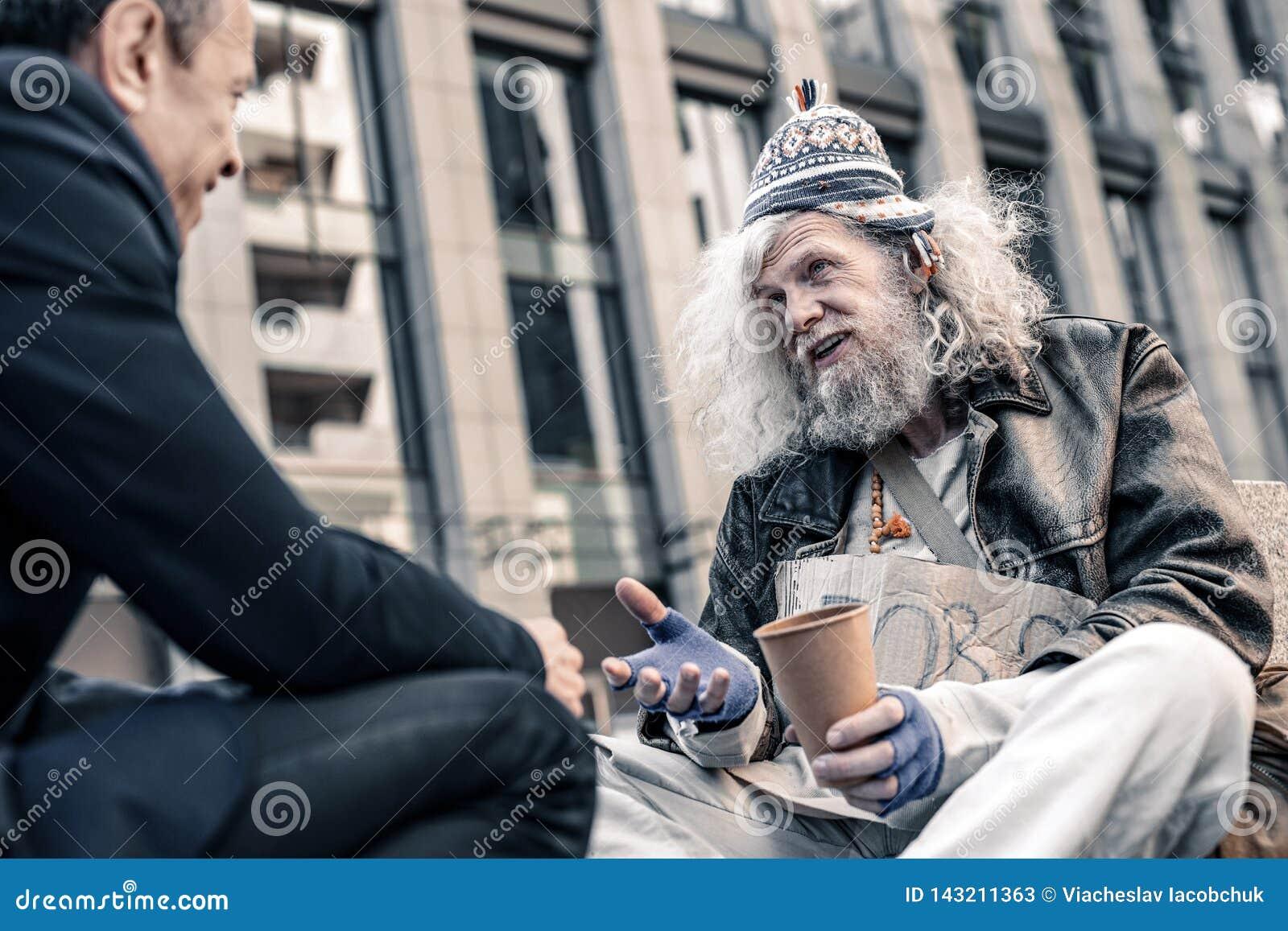 Pobre homem de cabelos compridos grato que agita a mão do pedestre generoso