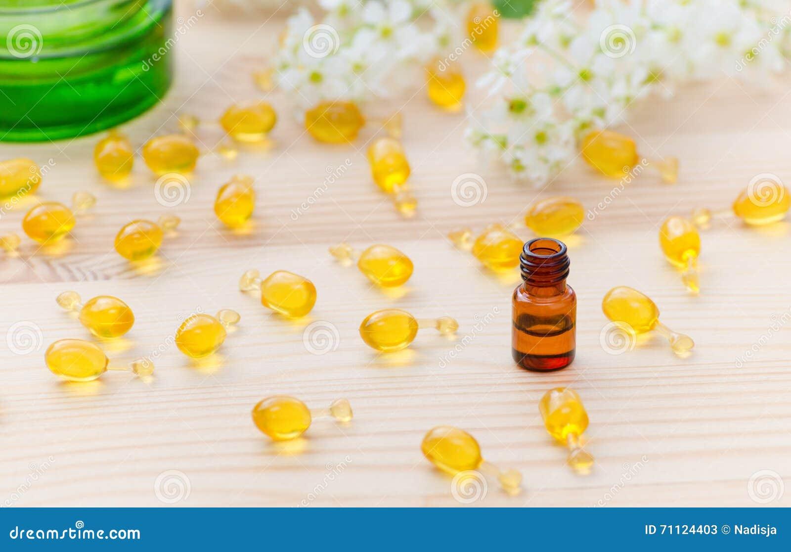 Poca botella marrón con aceites esenciales del neroli, las cápsulas del oro de cosmético natural y las flores florecen en el de m