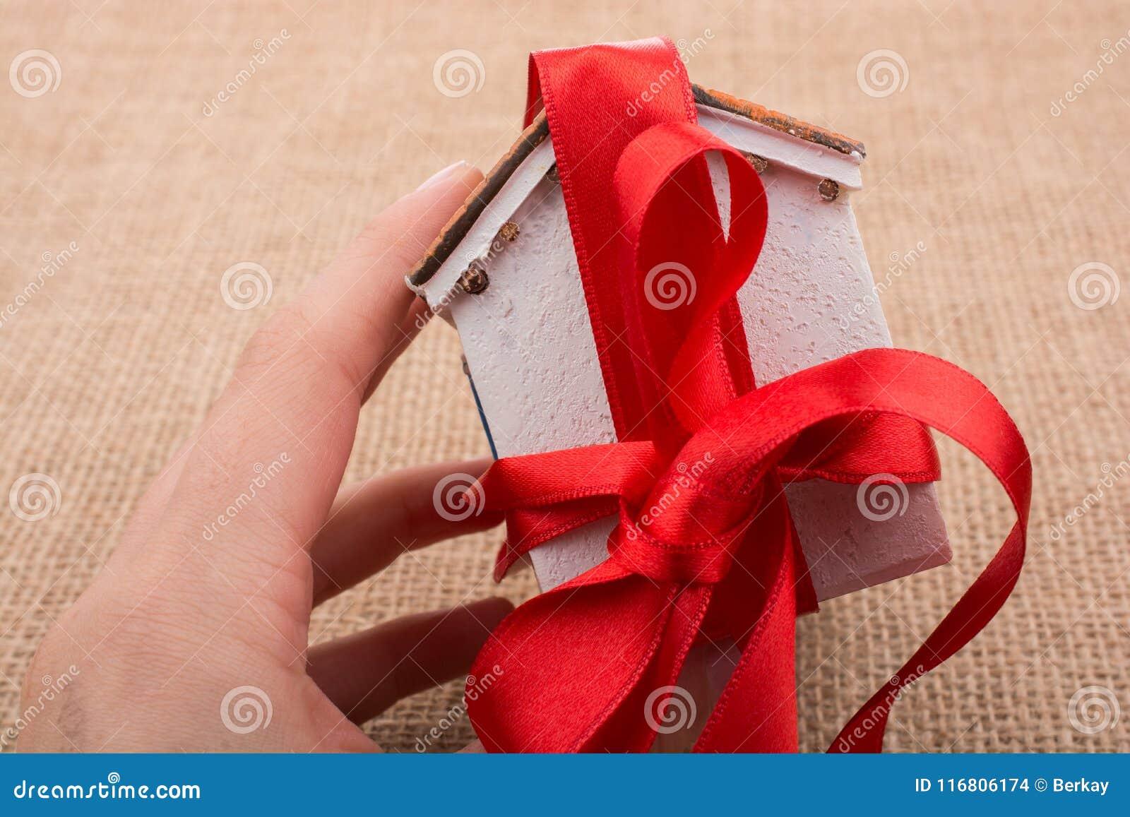 Poca casa di modello avvolta in nastro rosso