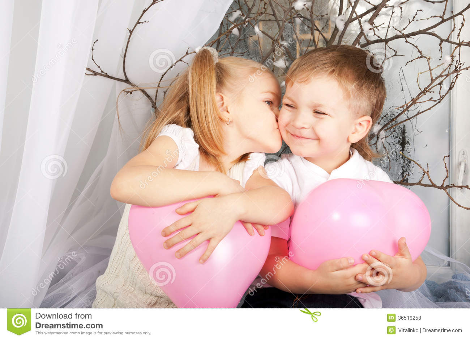 0ce14243a9 Poca coppia dei bambini che abbracciano, bacianti e tenenti il cuore  balloons. San Valentino e concetto di amore.