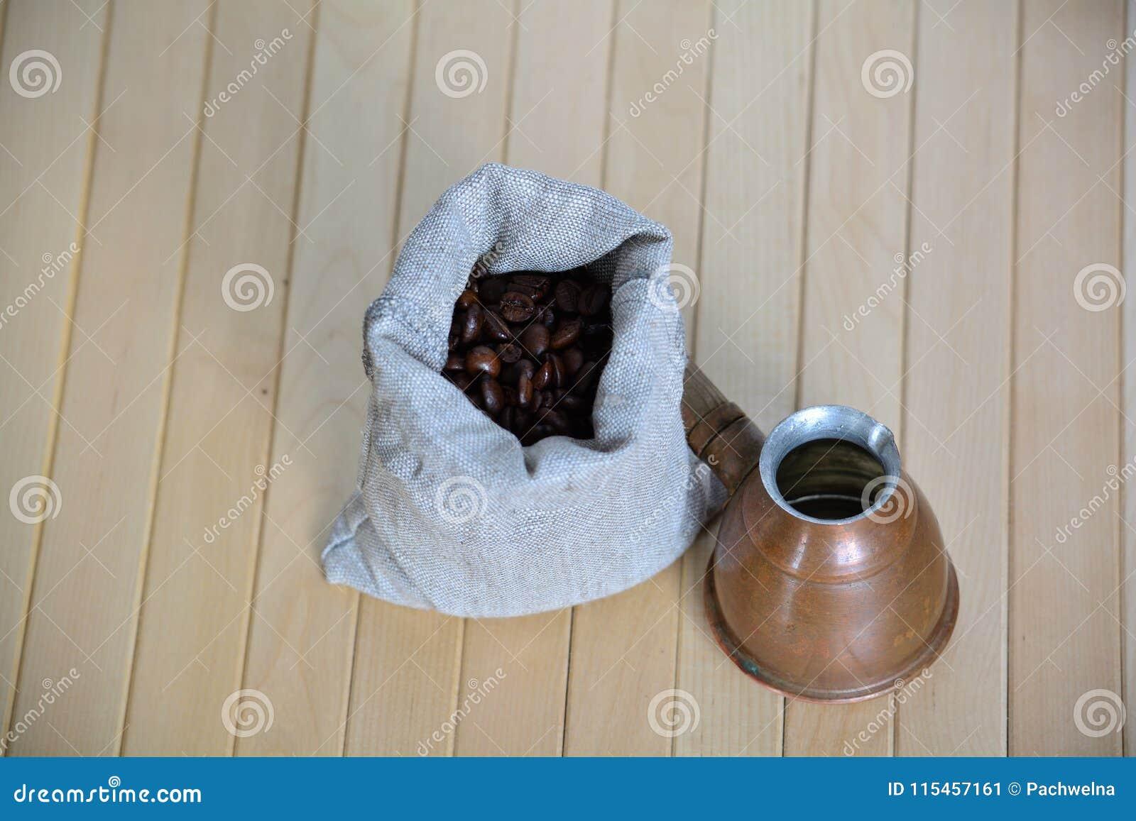 Poche des grains de café avec un pot turc de brassage