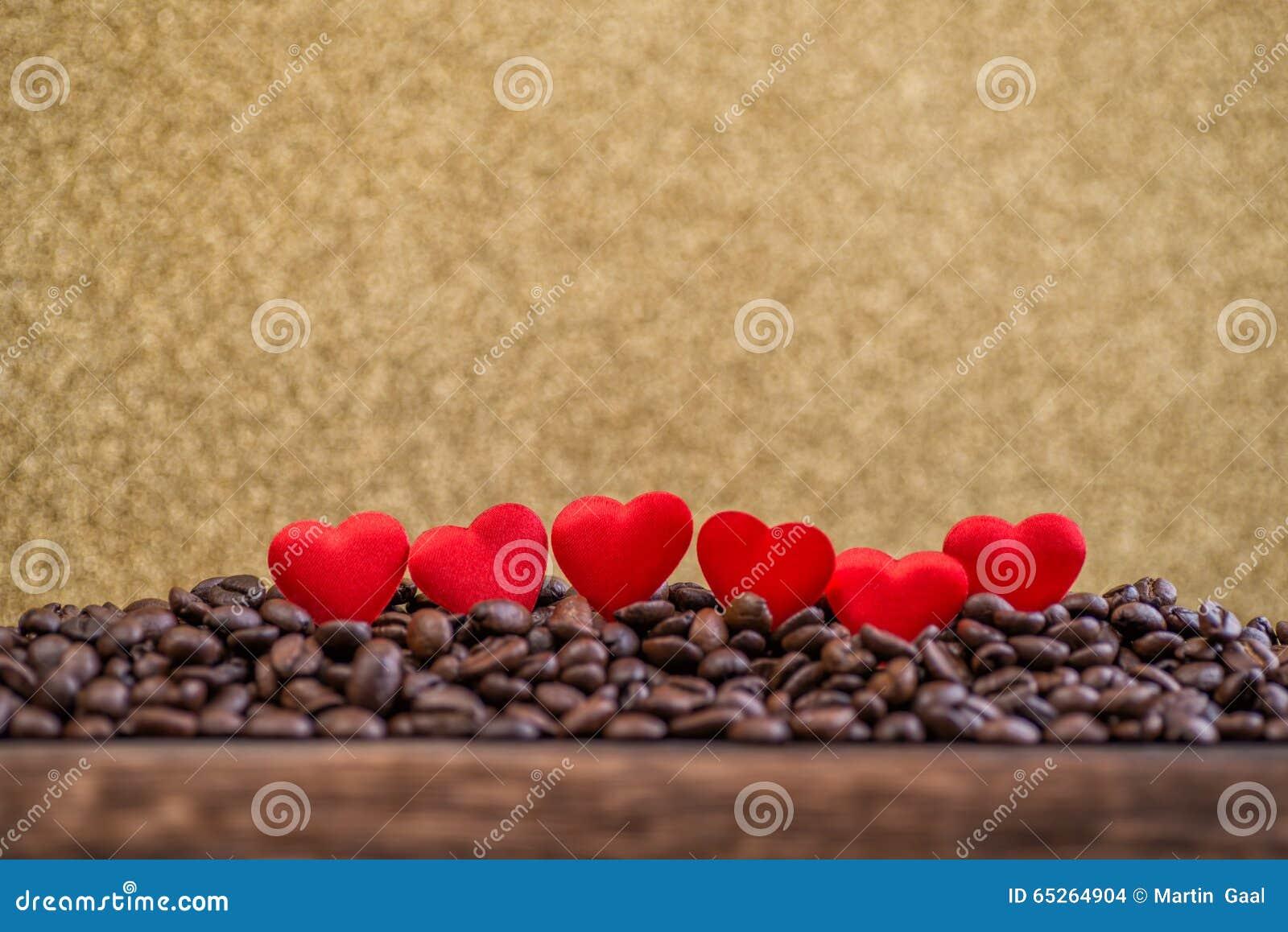 Pochi cuori rossi del raso con le lettere sui chicchi di caffè con il fondo dell oro, il giorno di biglietti di S. Valentino o la