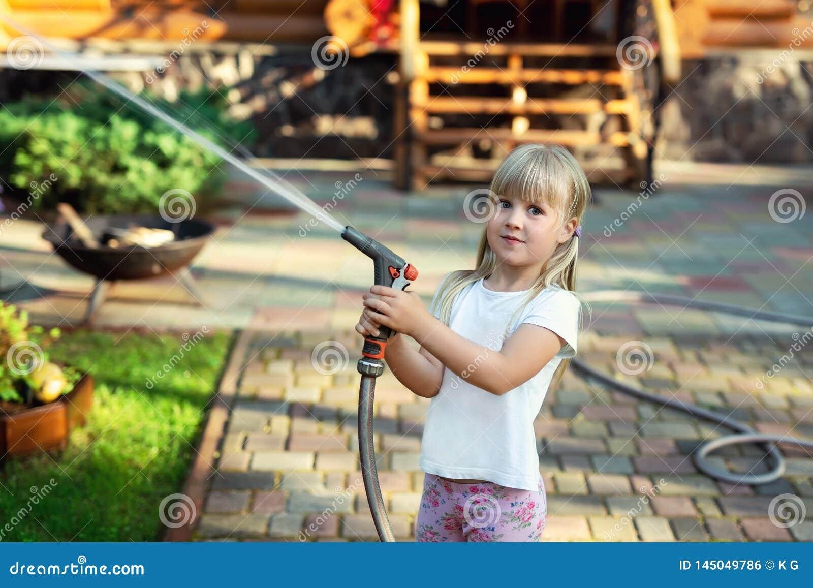 Poco bebé lindo que riega el simple patio trasero de la casa del césped fresco de la hierba verde en día de verano brillante N