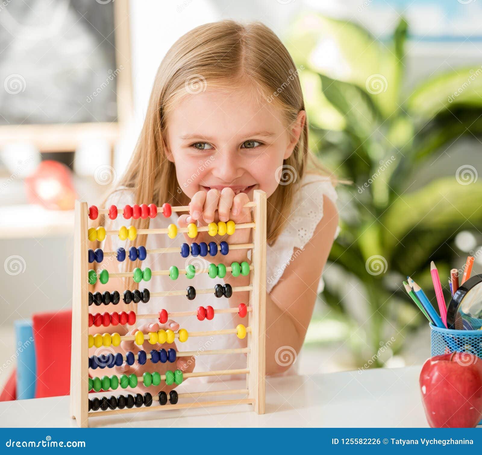 Poco contando en el ábaco colorido en la sala de clase de la escuela