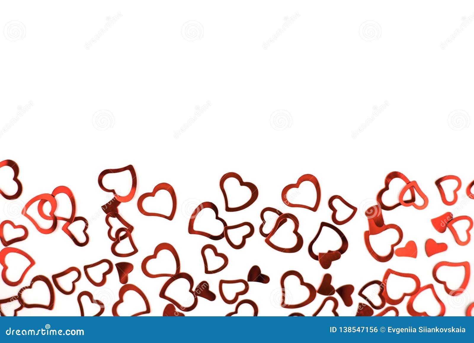 Poco corazones rojos del confeti en el fondo blanco