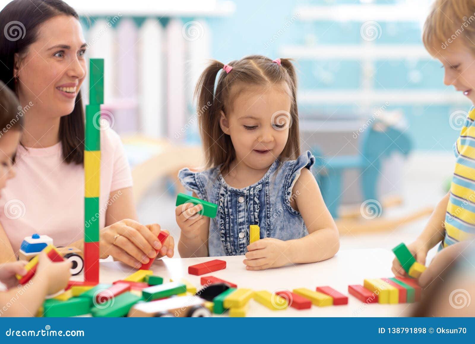 Poco juguetes de la unidad de creación de los niños en casa o guardería Niños que juegan con los bloques del color Juguetes educa