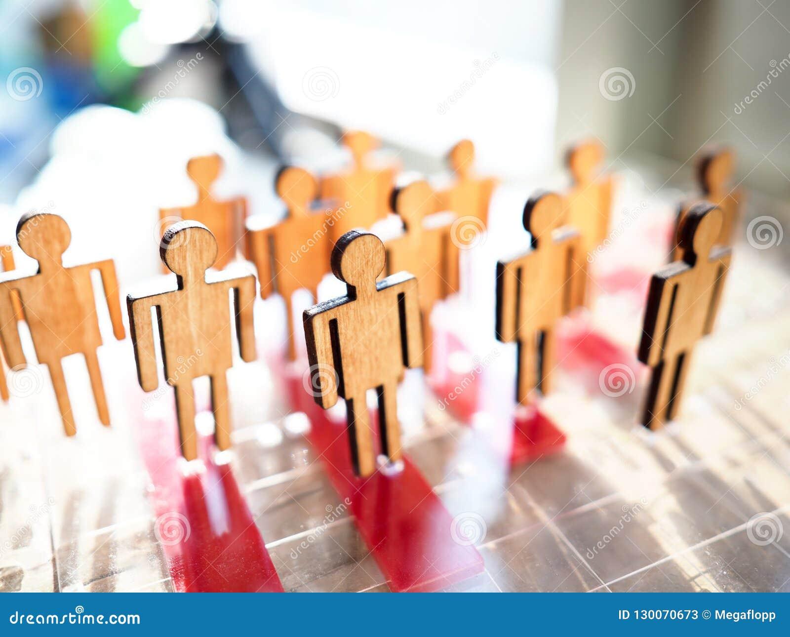 Poco las figuras de madera de la gente del juguete se coloca en fila