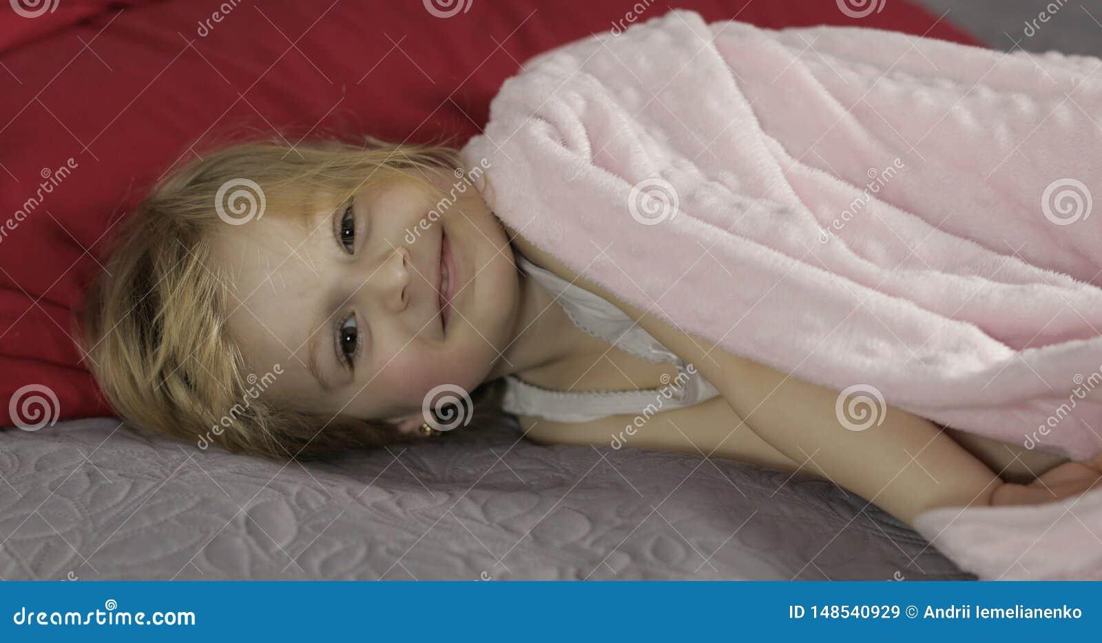 Poco muchacha alegre debajo de una manta en cama en casa Bastante, ni?a