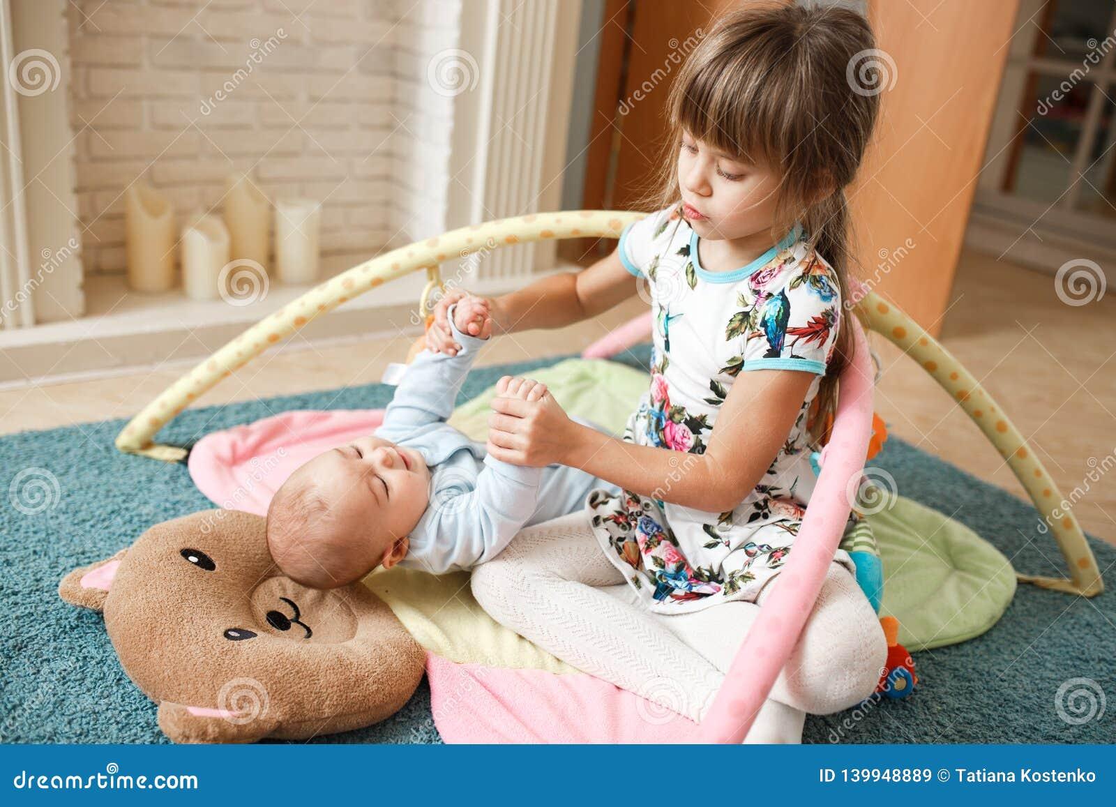 Poco muchacha encantadora lleva a cabo las manos su hermano minúsculo que miente en la alfombra en el piso en el cuarto