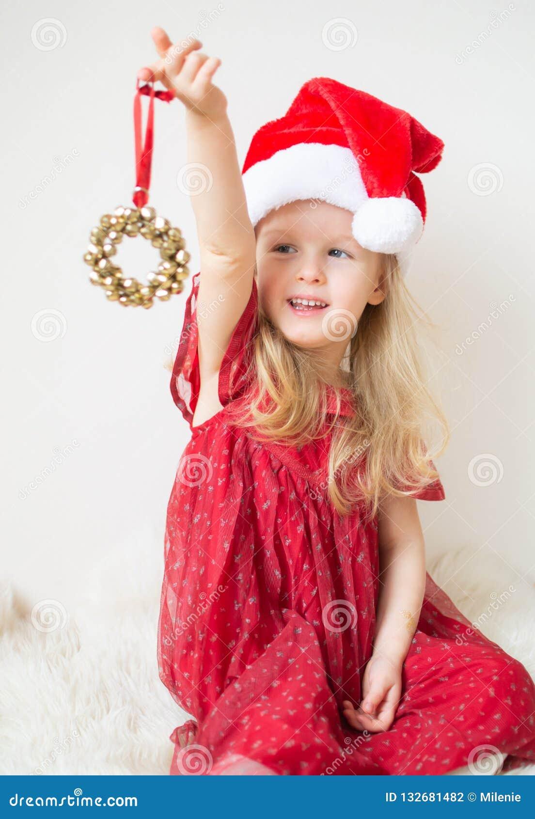Poco muchacha hermosa en la Navidad que espera de Santa Hat Red Party Dress para y el Año Nuevo