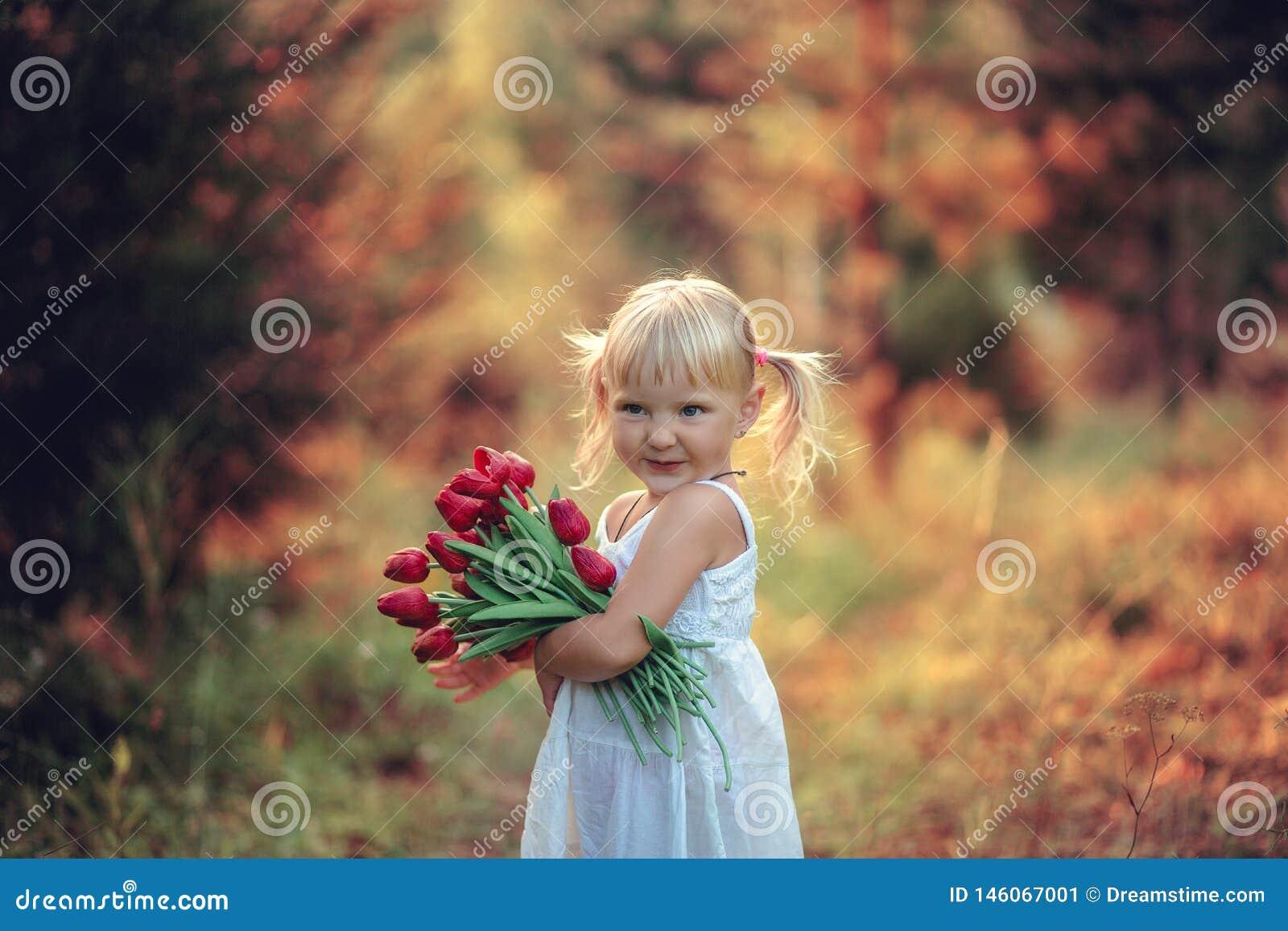Poco muchacha hermosa que sonríe con las colas en su cabeza en el vestido blanco con un ramo de tulipanes