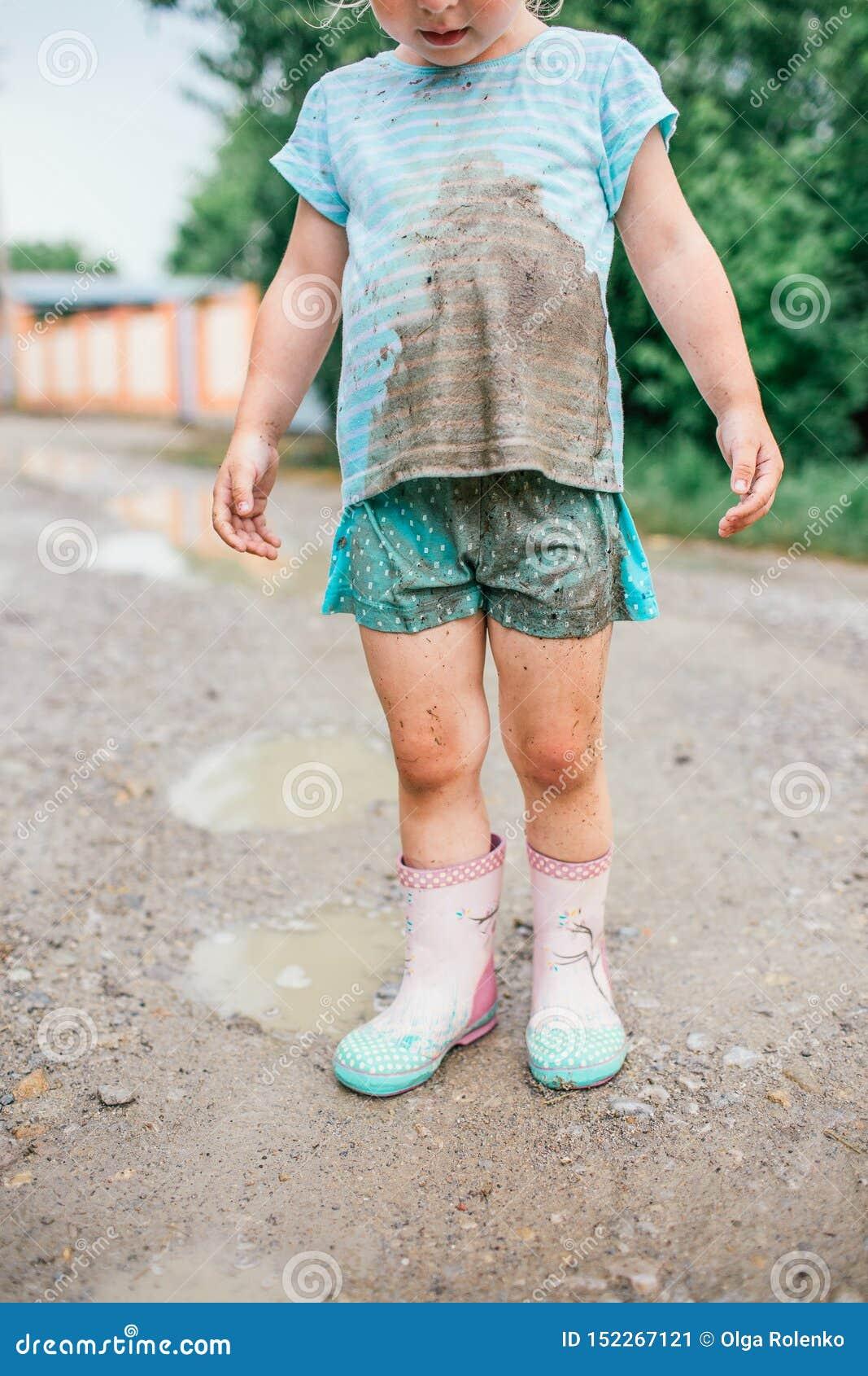 Poco muchacha rubia mira su ropa sucia después de caída en un charco