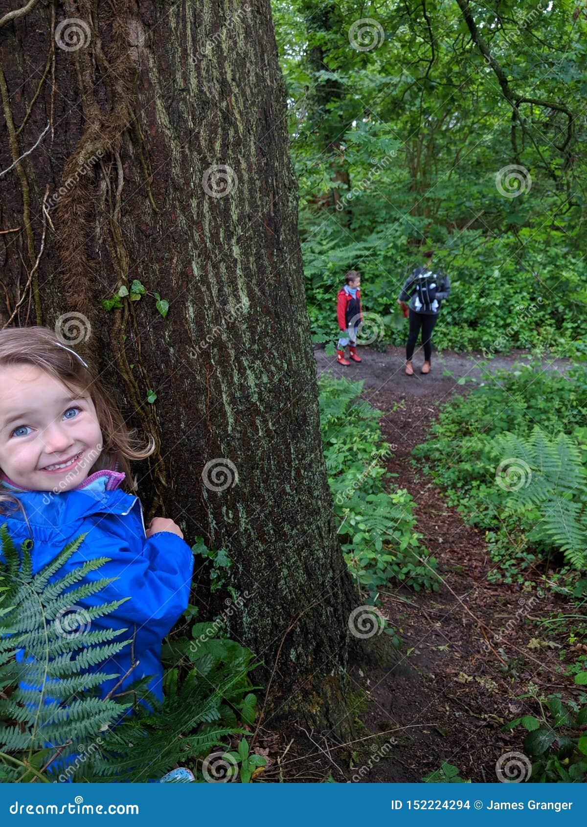 Poco muchacha sonriente juega escondite con su familia