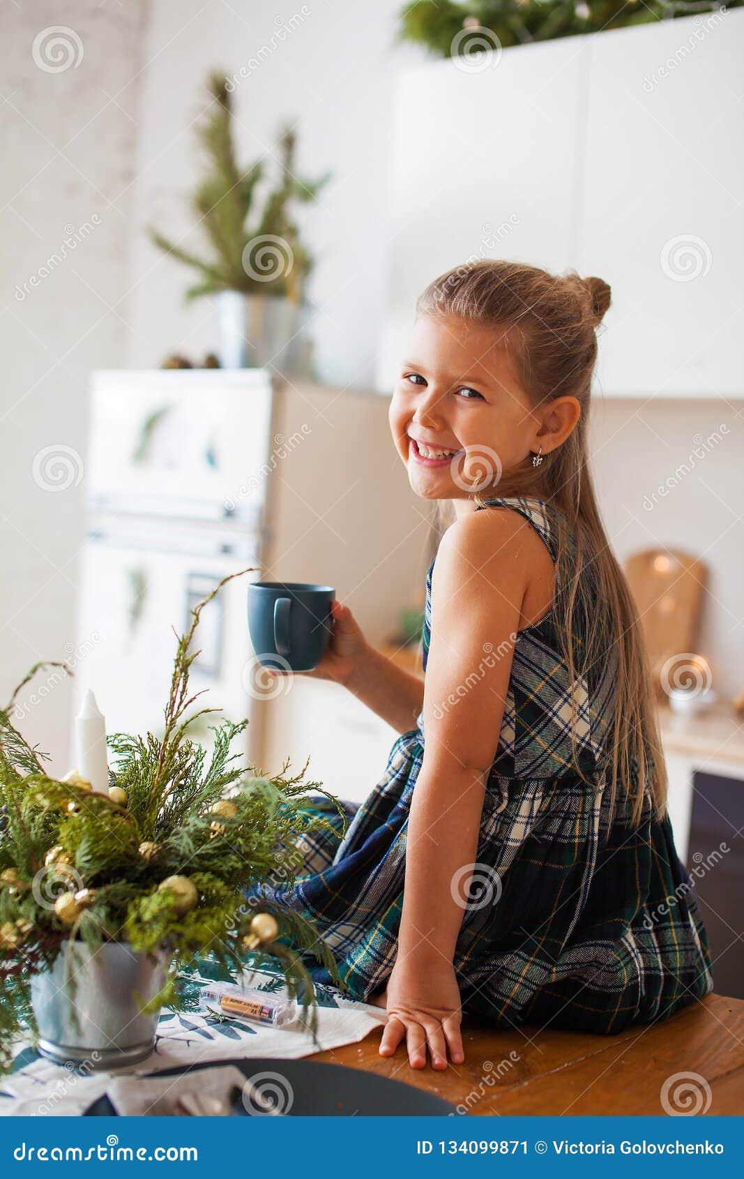 Poco muchacha sonriente que sostiene un casquillo que se sienta en la tabla en cocina en decoraciones de la Navidad