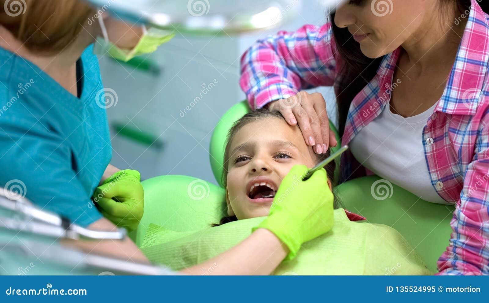 Poco muchacha valiente que visita el stomatologist pediátrico, examen de los dientes de leche