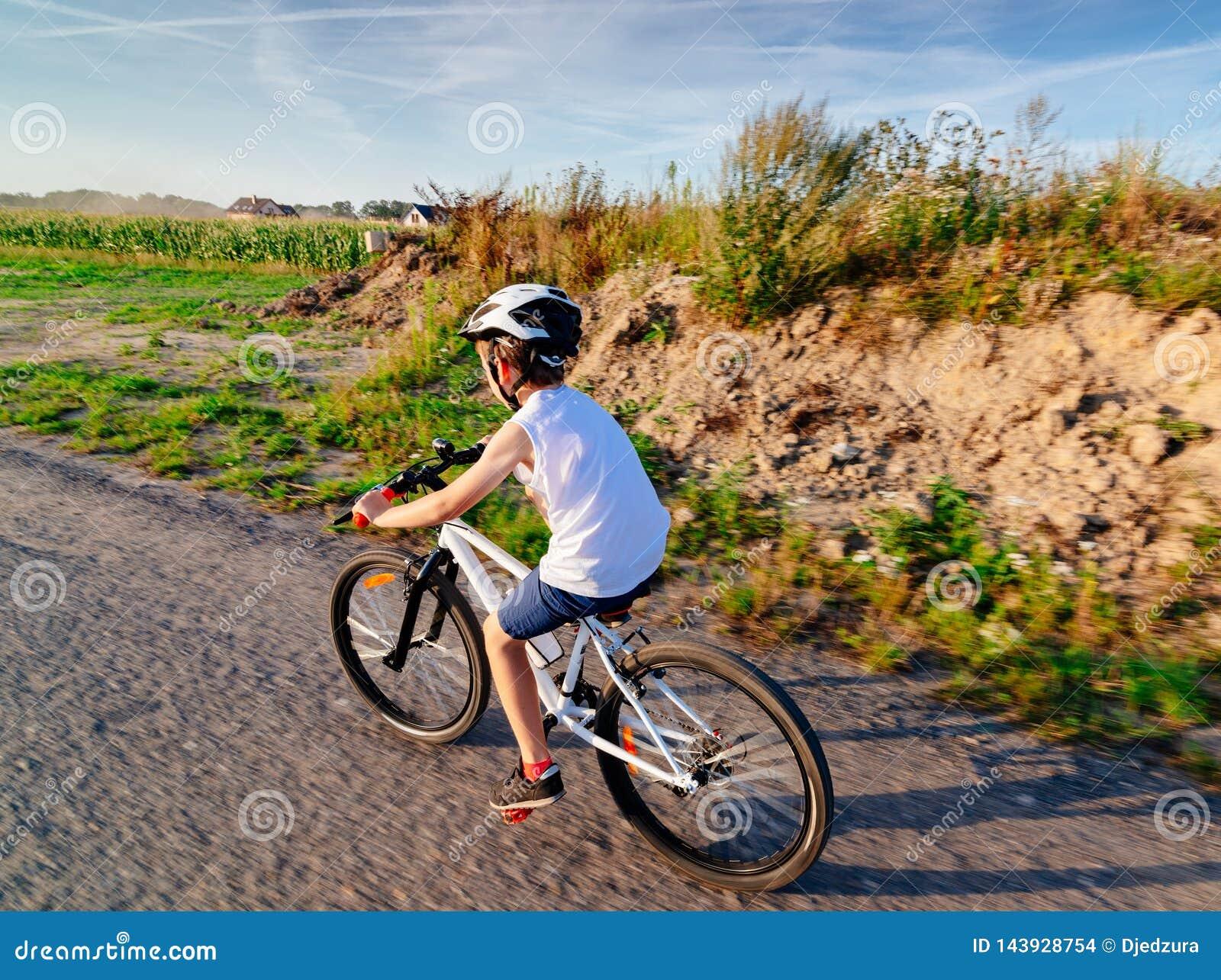 Poco muchacho del ni?o en el casco blanco que monta su bicicleta