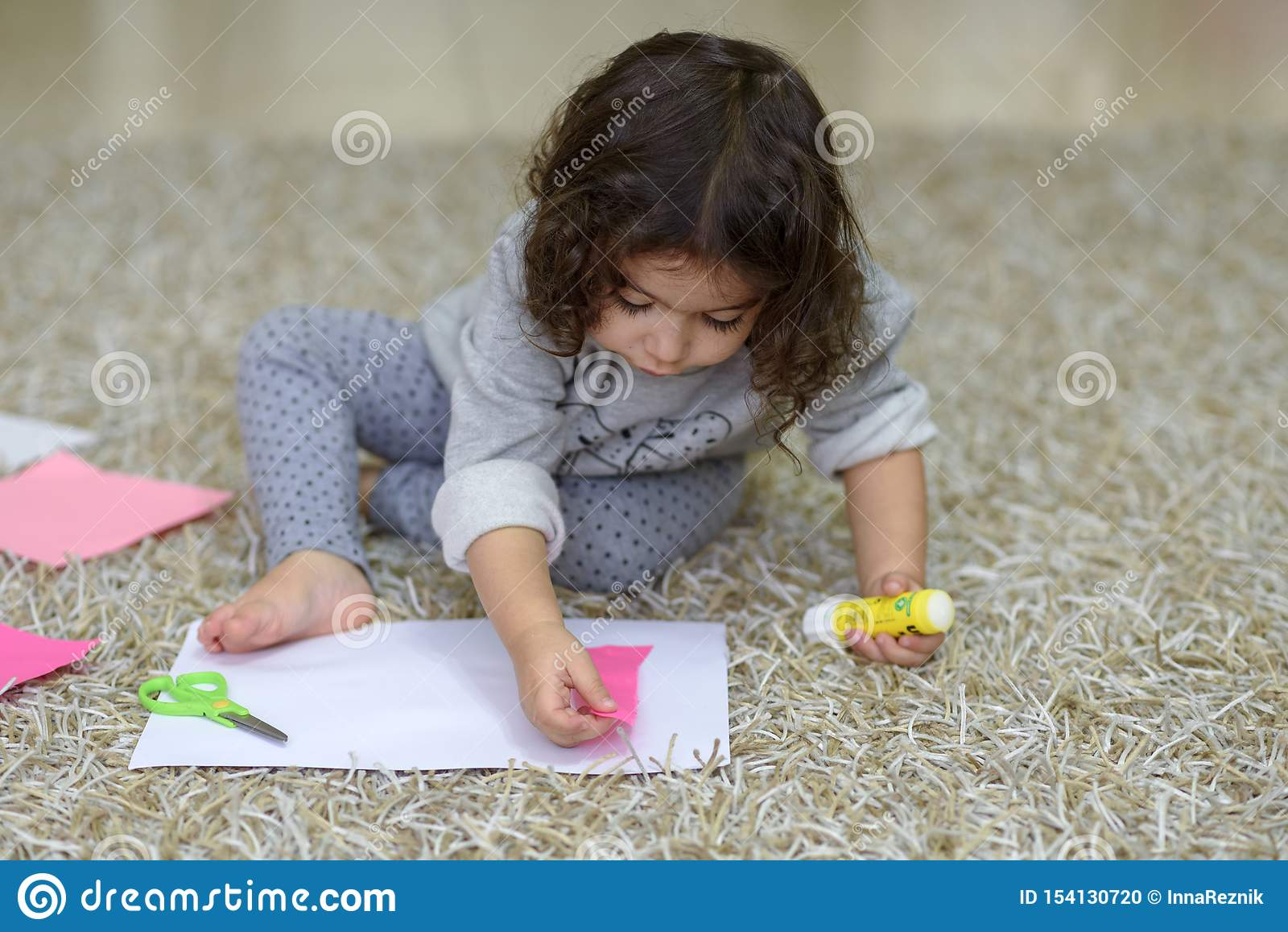 Poco niña pequeña del preescolar que pega el papel colorido