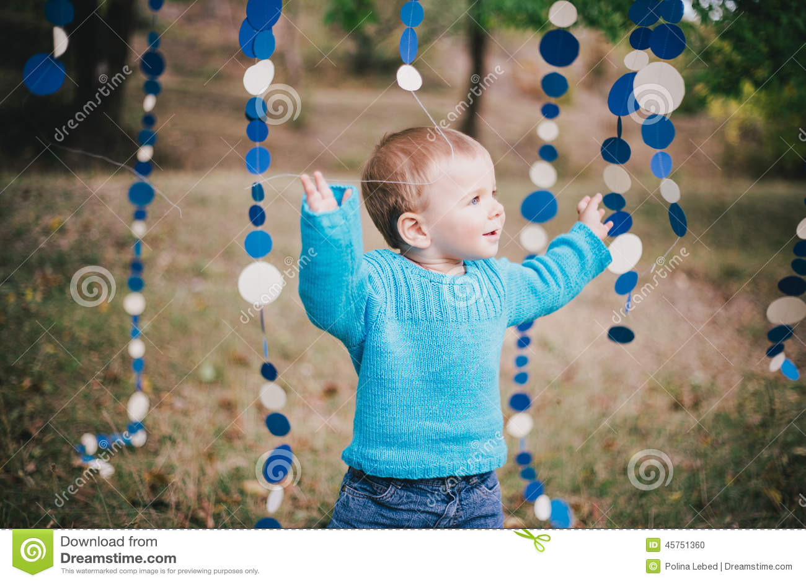 Poco ragazzo di modo in una foresta che indossa maglione e jeanse blu