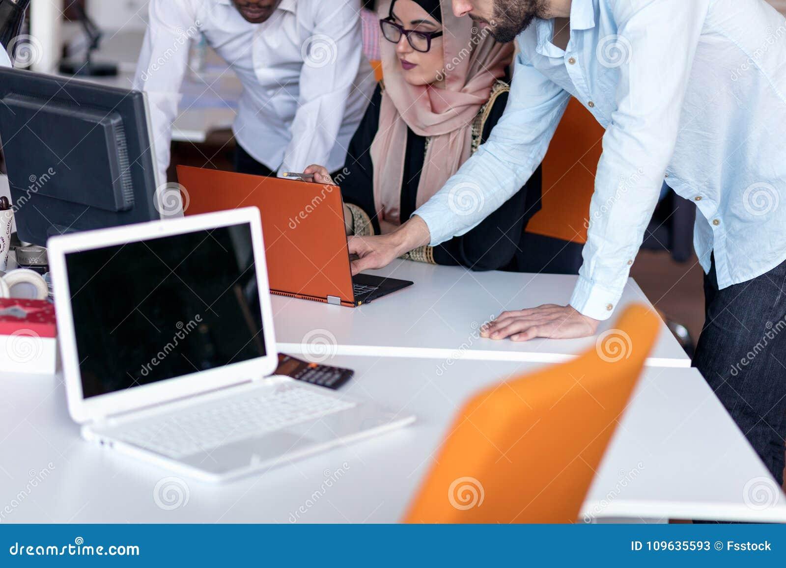 Początkowa biznes drużyna na spotkaniu w nowożytnym jaskrawym biurowym wewnętrznym brainstorming, pracujący na laptopu i pastylki