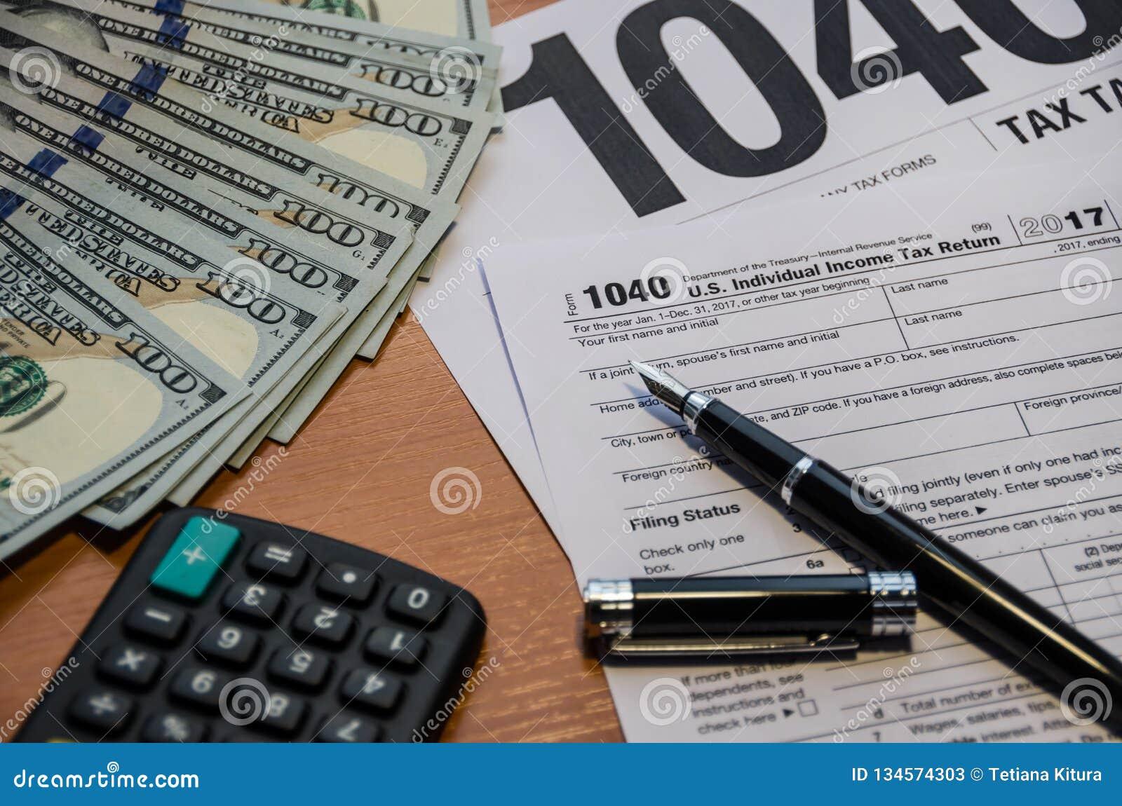 Podatek forma 1040, pióro, dolary, kalkulator na stole