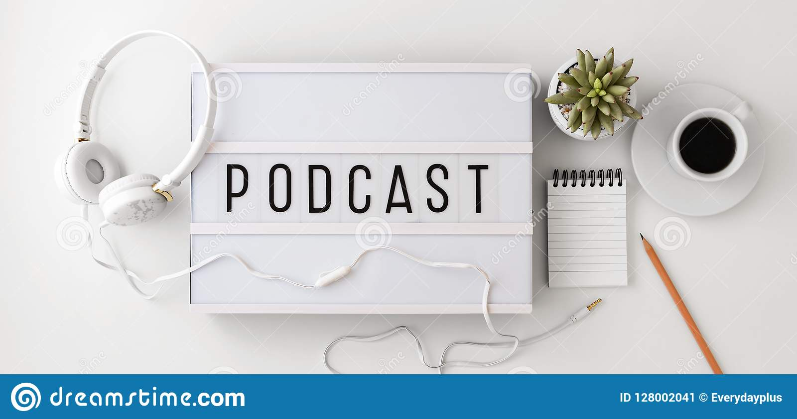 Podcast concept with headphones, notepad on white background, flat lay