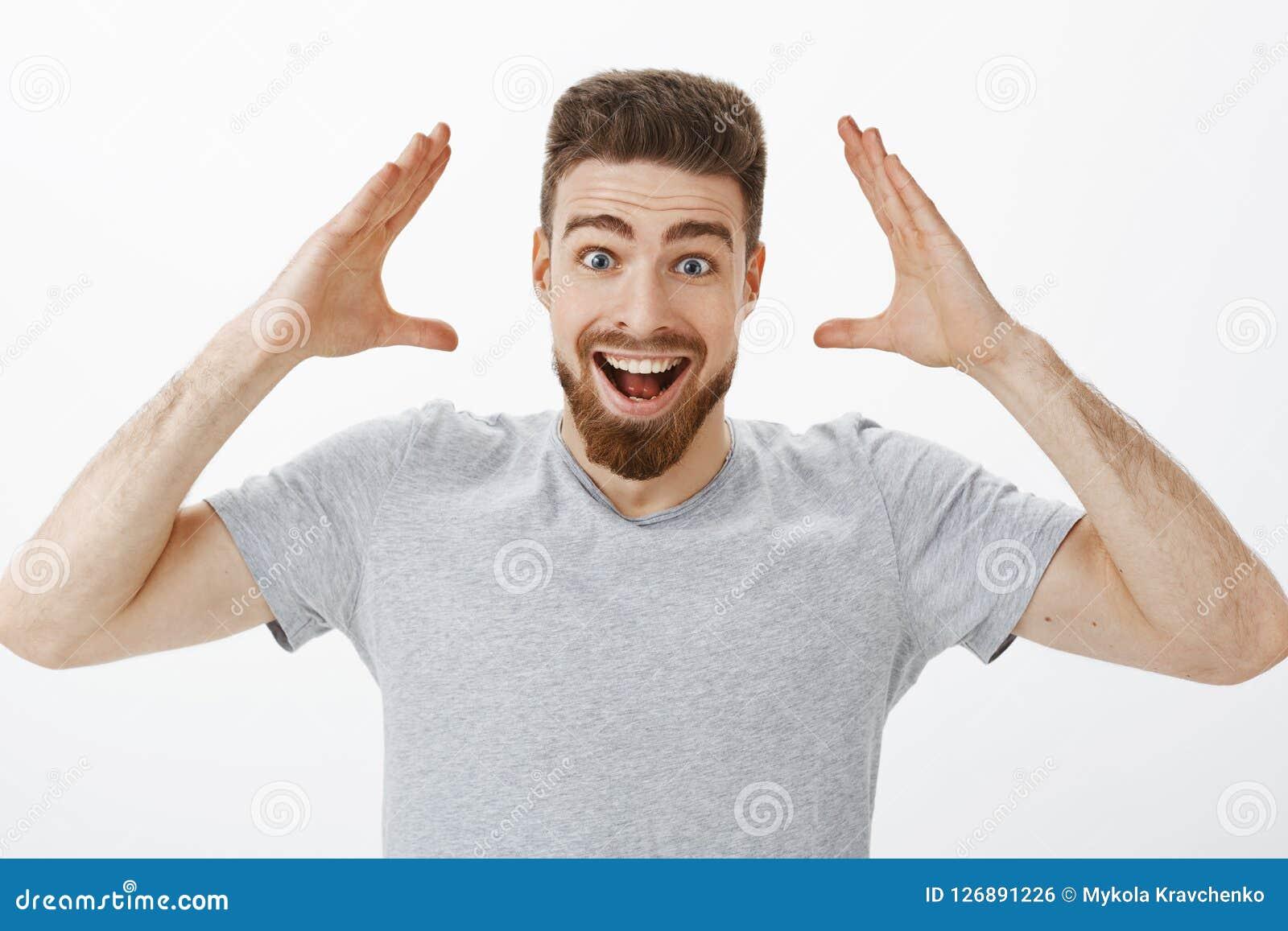 Pode você imaginar-me obteve o trabalho Modelo masculino considerável alegre e entusiasmado carismático com a barba no t-shirt ci