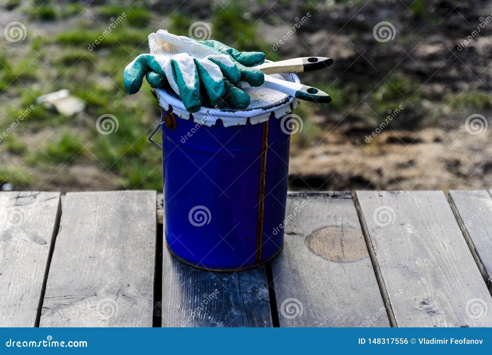 Poder de la pintura que miente en la terraza de una casa privada con un cepillo y los guantes, lista para ser abierto y para ser