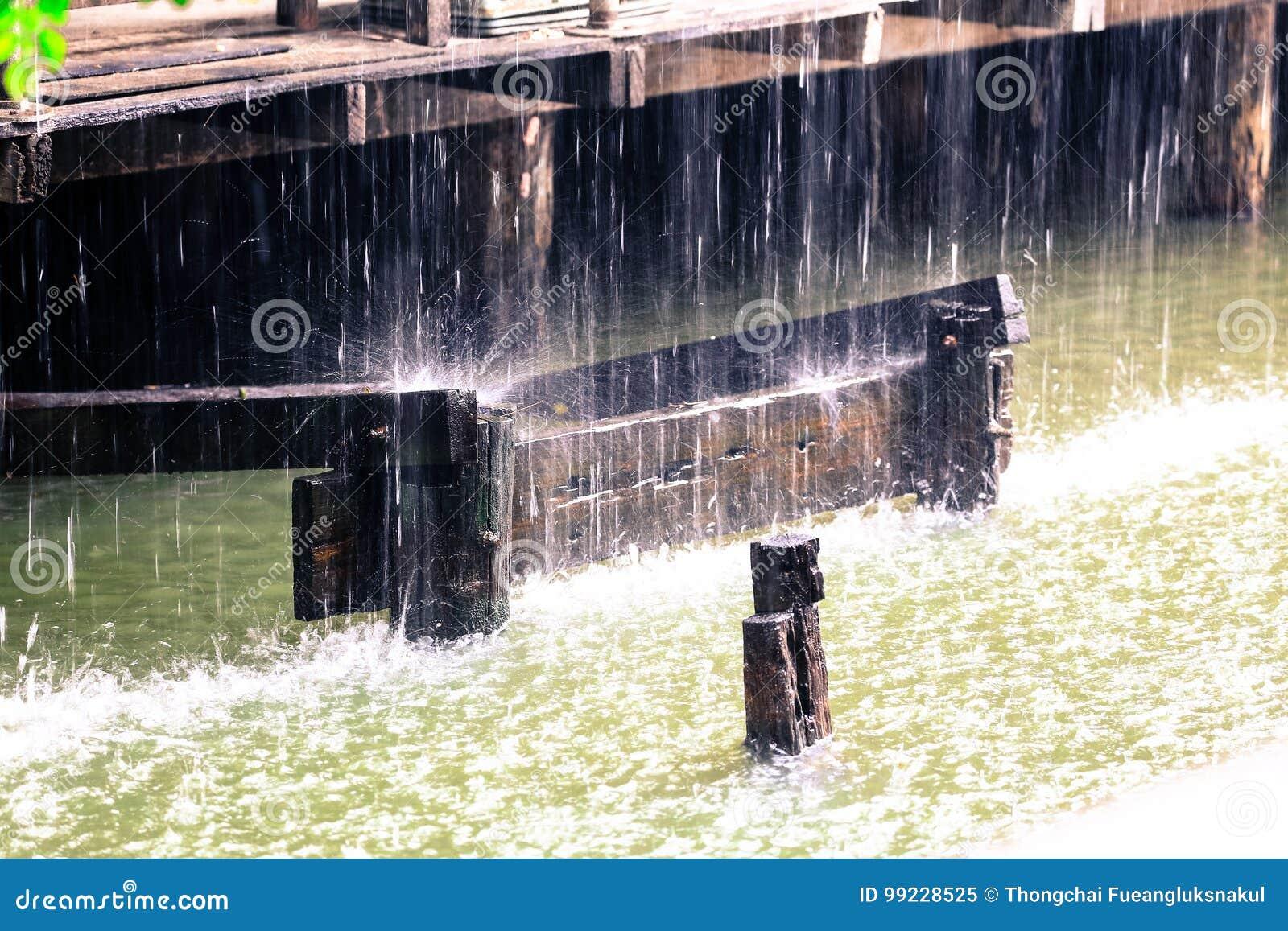 Podeszczowa kropla w wodzie z rocznika drewnianym domem na kanale