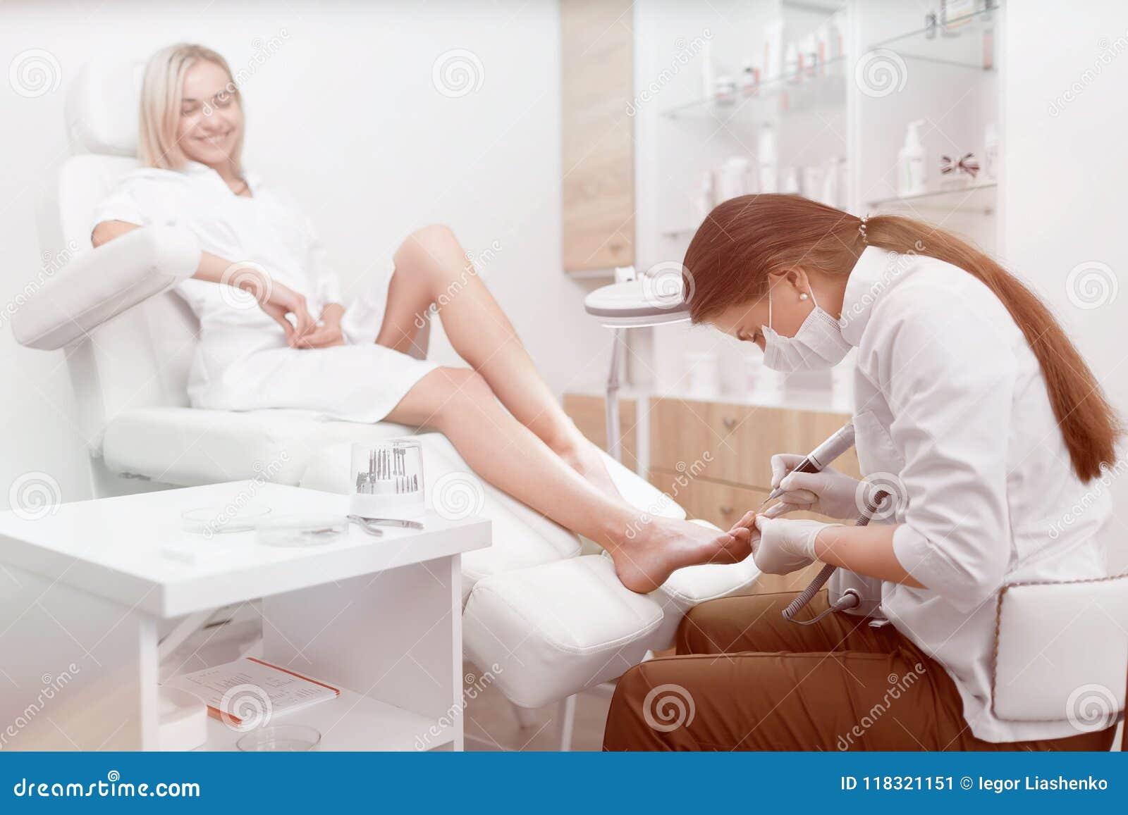 Podiatrist που κάνει τη διαδικασία για το πόδι πελατών