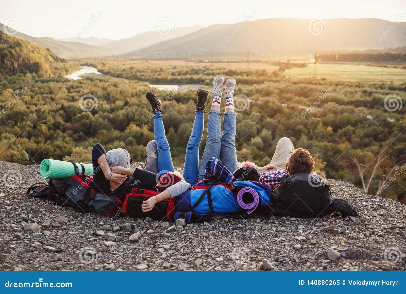 Podróżować, turystyki i przyjaźni pojęcie, Grupa młodzi przyjaciele podróżuje wpólnie w górach Szczęśliwy modniś