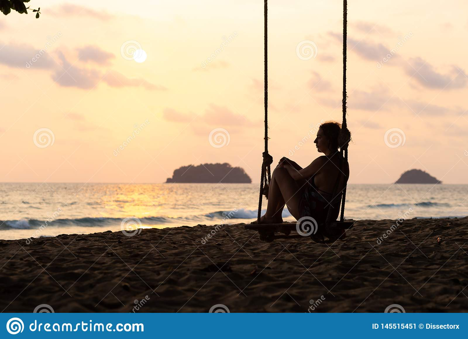 Podr?? bloga fotografia: Sylwetka kobieta w sukni podczas zmierzchu z widokiem nad morzem z ma?ym isand na horyzoncie